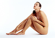 Profile of a nude woman sitting on a white background with legs crossed