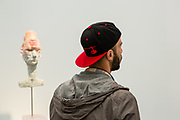 New York, NY - 5 May 2017. The opening day of the Frieze Art Fair, showcasing modern and contemporary art presented by galleries from around the world, on Randall's Island in New York City. A man appears to be looked at by a mixed-media head by David Altmejd in the gallery of Xavier Hufkens.