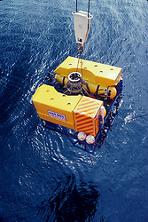 Stock photo of an Underwater Remote Operated Vehicle being placed into the ocean from and offshore drilling rig