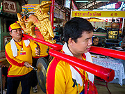 """02 JUNE 2017 - SAMUT SAKHON, THAILAND:  Procession participants bang a gong alerting people to the start of the City Pillar Shrine parade in Samut Sakhon. The Chaopho Lak Mueang Procession (City Pillar Shrine Procession) is a religious festival that takes place in June in front of city hall in Samut Sakhon. The """"Chaopho Lak Mueang"""" is  placed on a fishing boat and taken across the Tha Chin River from Talat Maha Chai to Tha Chalom in the area of Wat Suwannaram and then paraded through the community before returning to the temple in Samut Sakhon. Samut Sakhon is always known by its historic name of Mahachai.     PHOTO BY JACK KURTZ"""