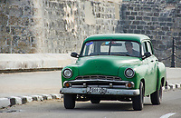 Havana, Cuba - A taxi passes in front of Castillo de San Salvador de la Punta on the Malecón road facing Havana Bay. Classic American cars from the 1950s, imported before the U.S. embargo, are commonly used as taxis in Havana.