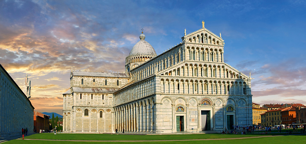 View of the Romanesque Duomo of Pisa at sunset . Pisa Cathedral is a medieval Roman Catholic cathedral dedicated to the Assumption of the Virgin Mary, in the Piazza dei Miracoli in Pisa, Italy. It is a notable example of Romanesque architecture, in particular the style known as Pisan Romanesque.It is the seat of the Archbishop of Pisa. Construction on the Pisa cathedral began in 1063, in the early 12th century the cathedral was enlarged under the direction of architect Rainaldo.