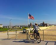 Spring Lake, NJ -- July 16, 2018. A police woman patrols the Spring Lake boardwalk on bicycle