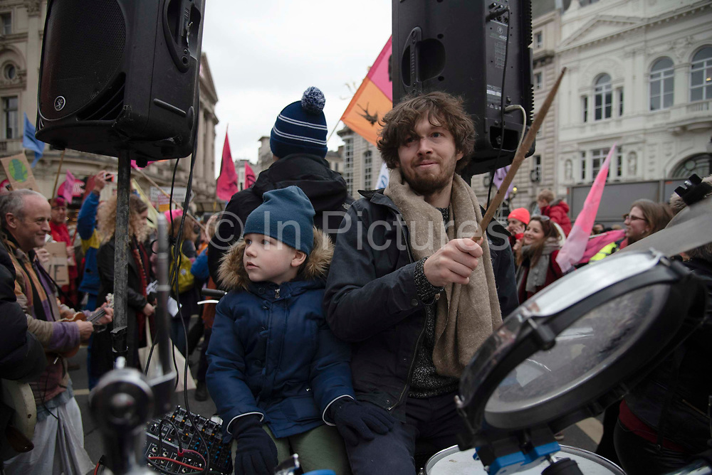 A climate change activist from Extinction Rebellion plays the drums on a cart at Piccadilly to say 'Enough is Enough' to inaction on the climate and ecological emergency on 22nd February 2020 in Central London, United Kingdom. Extinction Rebellion is a climate change group started in 2018 and has gained a huge following of people committed to peaceful protests. These protests are highlighting that the government is not doing enough to avoid catastrophic climate change and to demand the government take radical action to save the planet.
