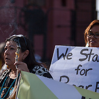 Anna Rondon with the Diné Latino Workers Coalition burns sages she leads the Martin Luther King day march from the Cultural Center to the Larry Brian Mitchell Recreation Center in Gallup Monday.