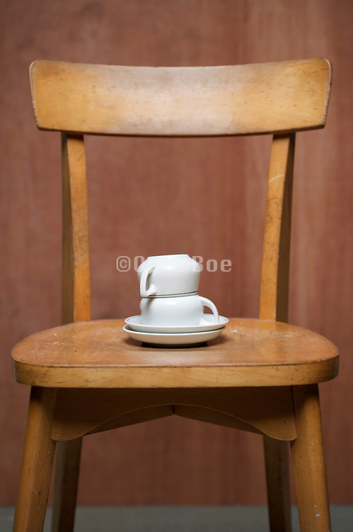 two coffee cups with saucer upside down on a chair