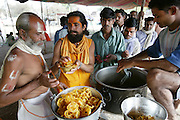 Ascetic sadhu holy men and other Hindu pilgrims eat a lunch of potato curry, dal, and chapatis provided by a local ashram during the Kumbh Mela festival in Ujjain, India. (Supporting image from the project Hungry Planet: What the World Eats).