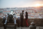 Tourists watching sunset and cityscape near an old canon at Saint George Castle, in Lisbon.