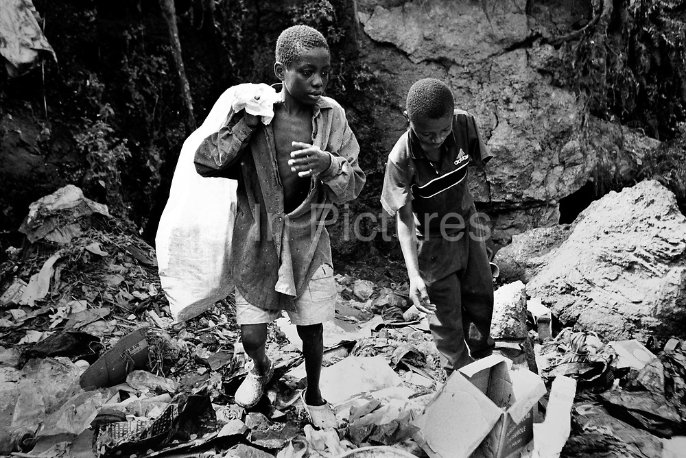 Siah and Mohammed (left) scavenge a city dump for plastic they can sell for recycling. Siah was amputated by the rebels and now lives on the streets. Freetown, Sierra Leone 2004<br /> Rebel forces, the Revolutionary United Front in Sierra Leone, systematically murdered, mutilated, and raped civilians during the country's civil war as a policy of terror