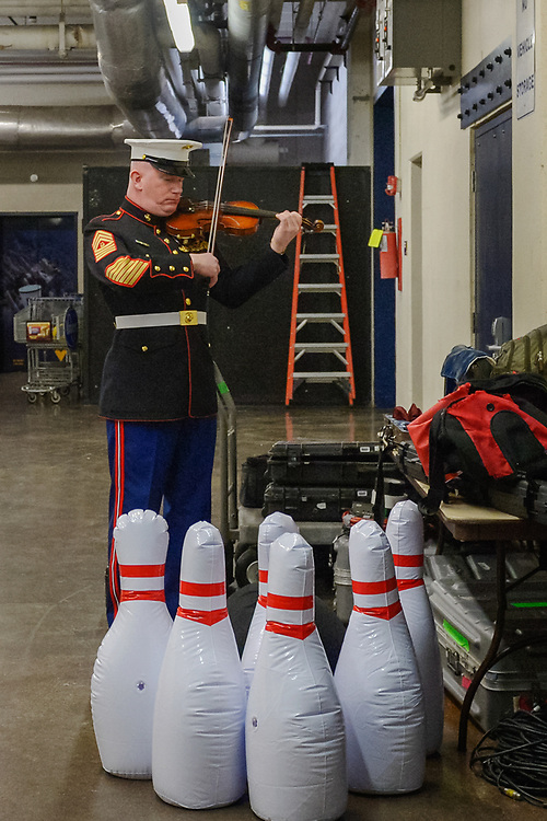 """Master Gunnery Sergeant Peter Wilson of """"The President's Own"""" United States Marine Band practices on his violin before performing the national anthem at an NCAA college basketball game in Morgantown, W.Va. on Saturday Feb. 9, 2019. (AP Photo/Craig Hudson)"""