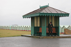 © under license to London News Pictures. 12/06/12. Heavy rainfall across the south east, a Man shelters from the rain on brighton seafront. The met office has issued severe weather warnings in England and Wales. Unseasonal weather in the south east has caused flooding. Sussex has been badly hit. Brighton XAVIER ITTER/LNP