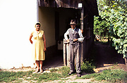 Full length portrait of elderly man and woman wearing yellow dress in rural countryside area, Romania, eastern Europe 1967