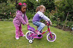 Two young girls playing in the garden with a bicycle,