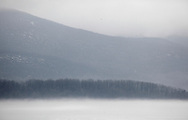 Newburgh, New York - Fog covers the Hudson River and clouds cover the tops of the Hudson Highlands on the east side of the river on a warm winter day on Jan. 2, 2010.