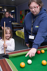 Adult teaching a child to play pool at Greenlane Youth Centre; Nottingham,