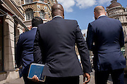 Three blue-suited businessmen walk along a City of London street holding identical blue spiral-bound notebooks.