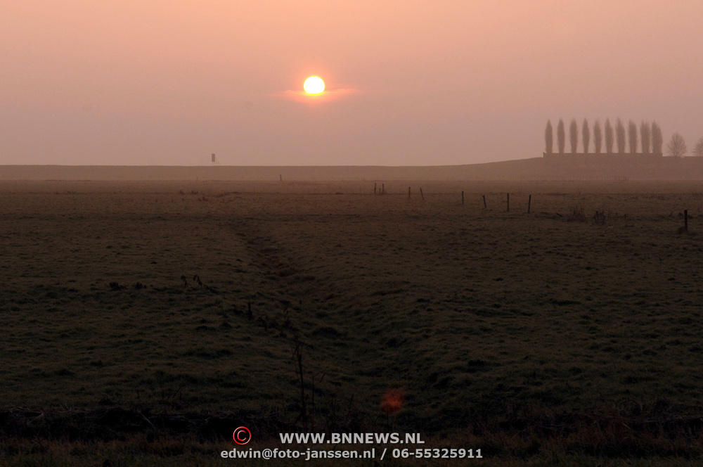 NLD/Huizen/20060113 - Ondergaande zon boven de weilanden Huizen, zonsondergang, opkomende, ochtend, avond, schemering
