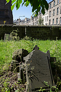 A broken gravestone for members of the same Notman family lies upright on the ground in Dalry cemetery on the Dalry Road in Edinburgh, on 26th June 2019, in Edinburgh, Scotland.