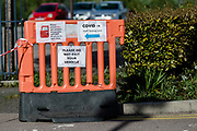 MERTHYR TYDFIL, WALES - 29 APRIL 2020 - Barrier with signs asking people not to exit their vehicles at a covid-19 virus testing area at Keir Hardie Health Park, Merthyr Tydfil.