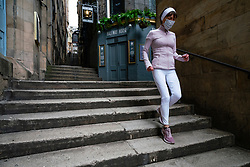 Edinburgh, Scotland, UK. 29 April 2020. Views of Edinburgh Old Town as coronavirus lockdown continues in Scotland. Streets remain deserted and shops and restaurants closed and many boarded up. Scottish Government now recommends public to wear face masks. Female jogger wearing face mask runs down steps in Fleshmarket Close. Iain Masterton/Alamy Live News