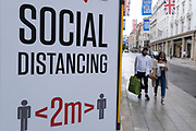 Social distancing signs on Bond Street under coronavirus lockdown on 1st July 2020 in London, England, United Kingdom. As the July deadline approaces and government will relax its lockdown rules further, the central London remains very quiet, while some non-essential shops are allowed to open with individual shops setting up social distancing systems.