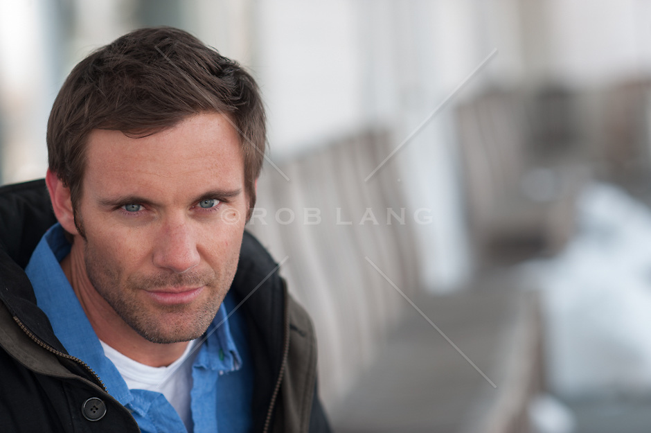 portrait of a handsome man with blue eyes and dark brown hair outdoors