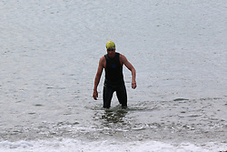 © Licensed to London News Pictures. 14/06/2014. Brighton, UK. Sea swimmer coming out of the water after a early morning swim. Brighton beach is readying itself for the flood of sun seekers and holiday makers. The weekend is expected to be the hottest of the year so far with temperatures reaching close to 30C down the south coast. Photo credit : Hugo Michiels/LNP