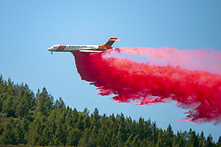 August 1, 2018 - Lakeport, California, US - An MD87 Air Tanker drops fire retardant on a ridge West of Scotts Valley Road near Lakeport, California to help hold a dozer line attempting to slow the spread of the River Fire burning in Lake and Mendocino Counties. The River Fire is one of two fires making up the Mendocino Complex Fire burning in northern part around the west end of Clear Lake, but both fires, the Ranch to the north and the River to the south, are still large and growing. Together they now total 90,912 acres and are still only 24% contained. (Credit Image: © Mark McKenna via ZUMA Wire)