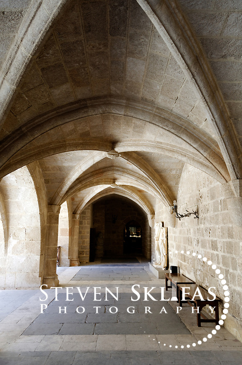 Rhodes. Greece. Gothic arches of the Palace of the Grand Masters central courtyard at Rhodes old town. The courtyard is paved with geometric marbles tiles and lined with ancient Hellenistic statues at Rhodes old town. Dating from the 14th century, the Palace of the Grand Masters is a fortress within the old town that was seat of government of the Grand Masters and nerve centre of the Knights quarter. It was restored in the 1930's by Italians for the intention of using it as a summer residence for Mussolini.