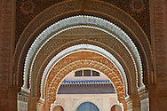 """Arabesque Moorish arches in the Palacios Nazaries Alhambra. Granada, Andalusia, Spain. . The Alhambra is a palace and fortress complex located in Granada, Andalusia, Spain. It was originally constructed as a small fortress in 889 CE on the remains of ancient Roman fortifications. The Alhambra was renovated and rebuilt in the mid-13th century by the Arab Nasrid emir Mohammed ben Al-Ahmar of the Emirate of Granada, who built its current Alhambra palace and walls. The Alhambra was converted into a royal palace in 1333 by Yusuf I, Sultan of Granada. The decoration of The Alhambra consists for the upper part of the walls, as a rule, of Arabic inscriptions—mostly poems by Ibn Zamrak and others praising the palace—that are manipulated into geometrical patterns with vegetal background set onto an arabesque setting (""""Ataurique""""). Much of this ornament is carved stucco (plaster) rather than stone. Tile mosaics (""""alicatado"""") of The Alhambra, with complicated mathematical patterns (""""tracería"""", most precisely """"lacería""""), are largely used as panelling for the lower part. .<br /> <br /> Visit our SPAIN HISTORIC PLACXES PHOTO COLLECTIONS for more photos to download or buy as wall art prints https://funkystock.photoshelter.com/gallery-collection/Pictures-Images-of-Spain-Spanish-Historical-Archaeology-Sites-Museum-Antiquities/C0000EUVhLC3Nbgw <br /> .<br /> Visit our ISLAMIC HISTORICAL PLACES PHOTO COLLECTIONS for more photos to download or buy as wall art prints https://funkystock.photoshelter.com/gallery-collection/Islam-Islamic-Historic-Places-Architecture-Pictures-Images-of/C0000n7SGOHt9XWI"""