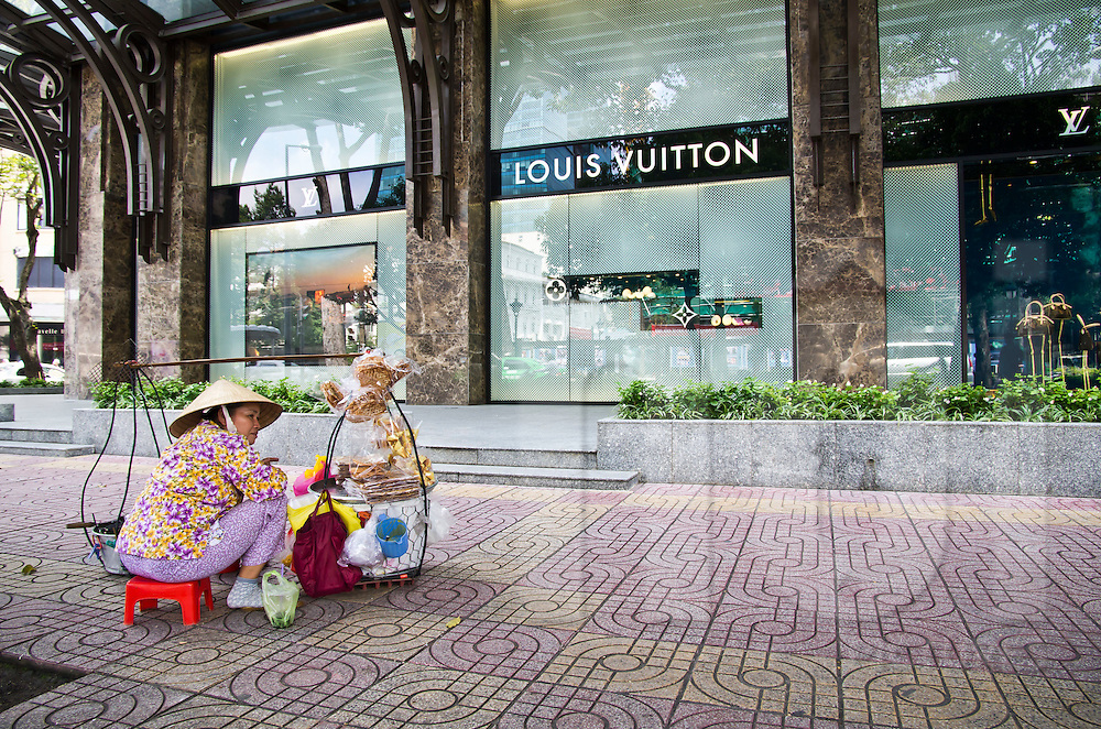 Vietnamese woman selling waffles in front of the Vuitton store in Dist.1,  Ho Chi Minh city (HCMC), Vietnam, Asia