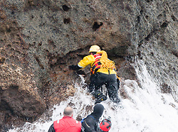 Nick Hancock (yellow) gets on Rockall, for his reconnaissance mission for a future 60 day occupation of Rockall. The Rockall Jubilee Expedition, a unique endurance expedition to be undertaken by Nick, in order to raise funds for Help for Heroes .©Michael Schofield..