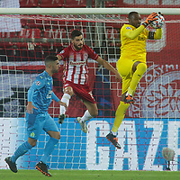 PIRAEUS, GREECE - OCTOBER 21: Steve Mandanda of Olympique de Marseille blocks in front of Giorgos Masouras of Olympiacos FC during the UEFA Champions League Group C stage match between Olympiacos FC and Olympique de Marseille at Karaiskakis Stadium on October 21, 2020 in Piraeus, Greece. (Photo by MB Media)