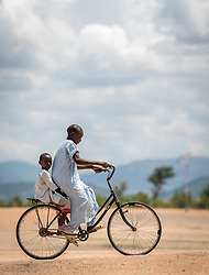 31 May 2019, Mokolo, Cameroon: Children ride a bike through the Minawao camp for Nigerian refugees. The Minawao camp for Nigerian refugees, located in the Far North region of Cameroon, hosts some 58,000 refugees from North East Nigeria. The refugees are supported by the Lutheran World Federation, together with a range of partners.
