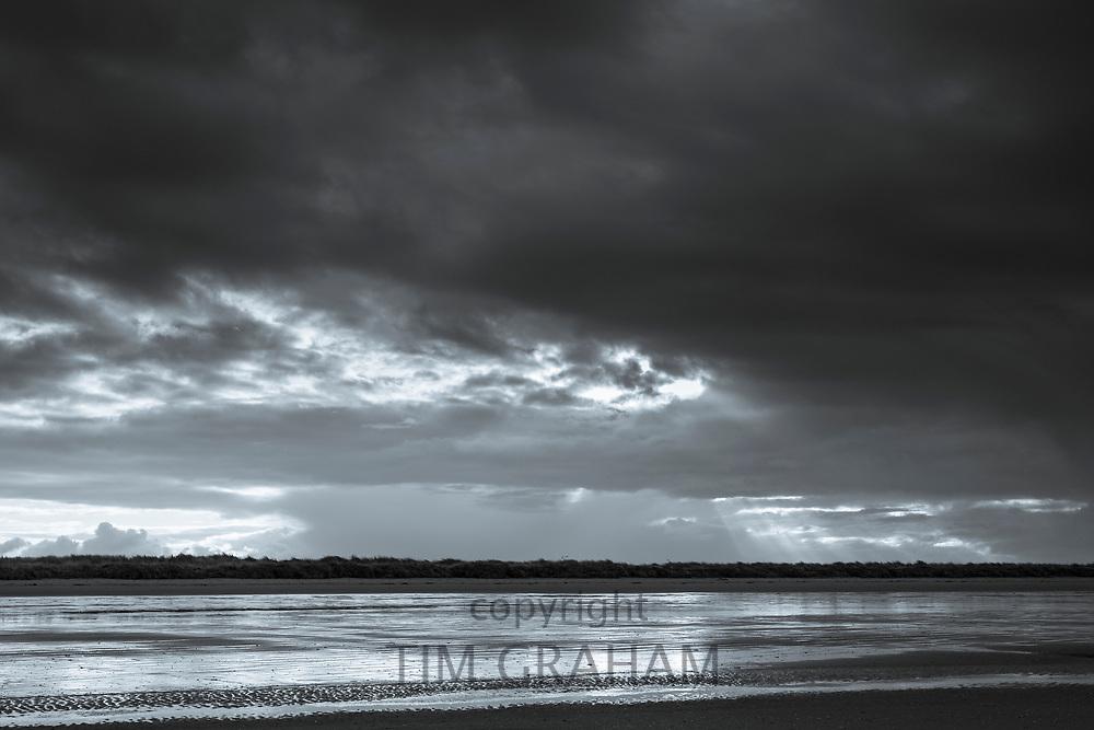Sun rays through cloudy skyscene - dark clouds and Norfolk coastal scene at Titchwell, North Norfolk, England, UK