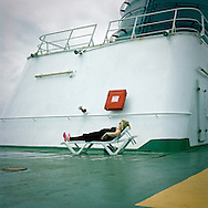 A woman sunbathes on the deck of the Pride of Bilbao passenger and car ferry as it  leaves the Basque port of Bilbao in northern Spain.