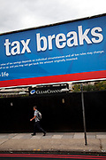Man walks past an advertising billboard poster in London asking to Apply Tax Breaks Now. In times of economic downturn and austerity measures all round, this seems an appropriate message.
