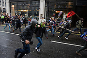 Young teenage students run from police against government education cuts in Regent Street. Holding a variety of placards that denounce the coalition government's policy of charging extra higher-education tuition fees, the atmosphere is excited and happy. But tens of thousands of students and school pupils walked out of class, marched, and occupied buildings around the country in the second day of mass action within a fortnight to protest at education cuts and higher tuition fees. There were isolated incidents of violence and skirmishes with police, mostly in central London among the 130,000 students.