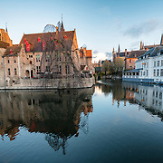 "Sometimes called ""The Venice of the North,"" the historic Flemish city of Bruges has canals running through the old town. Before the water access became silted up, Bruges was a major commercial port. The building at left of frame is the 15th century mayor's house, ""Perez de Malvenda""."