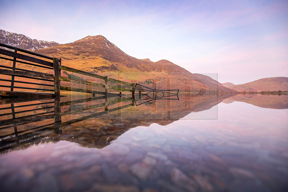 © Licensed to London News Pictures. 21/02/2018. GButtermere UK. The sky takes on a pink hue this morning at dawn as the mountains reflect in to the still water of Buttermere lake on a sunny day in Cumbria. Photo credit: Andrew McCaren/LNP