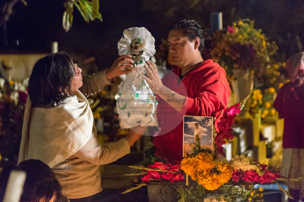 Family members arrange a Catrina doll to decorate a gravesite in honor of the dead at San Felipe de Aqua cemetery during the Day of the Dead Festival known in Spanish as Día de Muertos on November 2, 2013 in Oaxaca, Mexico.