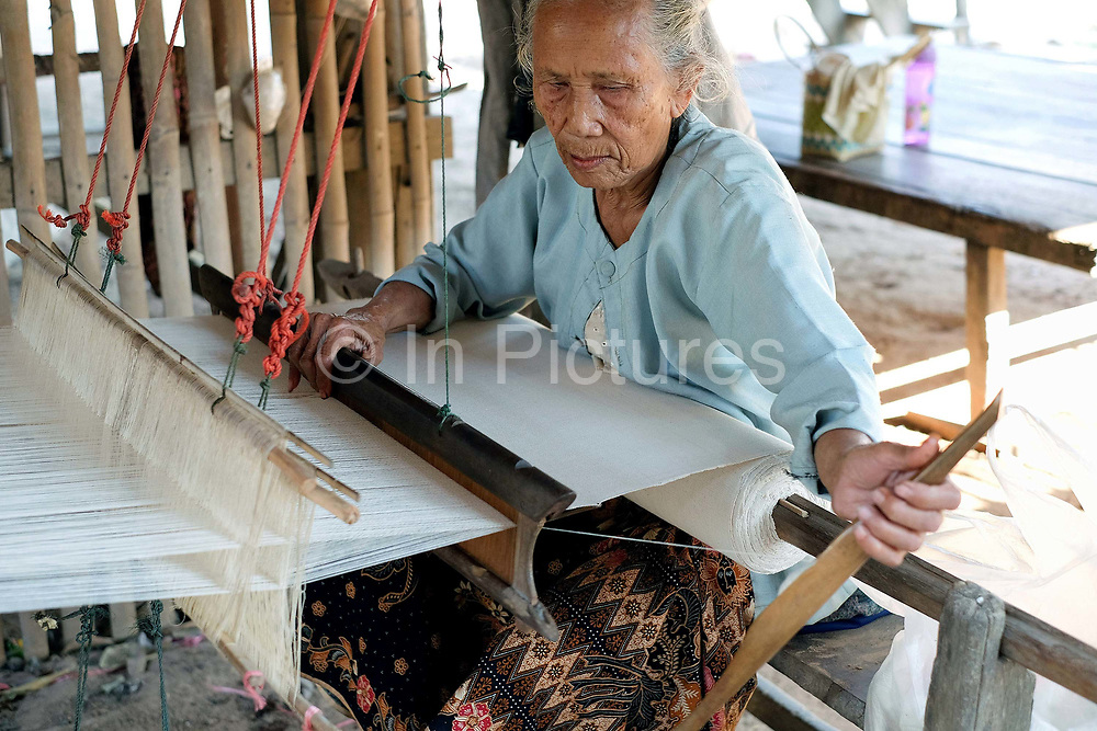 An elderly Phu Tai ethnic minority woman weaves handspun cotton, Ban Lahanam, Savannakhet province, Lao PDR. Cotton has been grown in Laos for centuries, mostly on a small scale for household use. The people of the Phu Tai ethnic group have a long standing tradition of cotton production which they hand weave for clothing and household use. Cotton is planted by hand and watered by the monsoon rains. It takes 8 months for the plant to produce the cotton flower, then it is picked by hand, ginned by hand and then spun into yarn by hand.