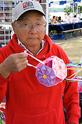 Asian man holding decorative hanging paper lantern sold at his booth. Dragon Festival Lake Phalen Park St Paul Minnesota USA