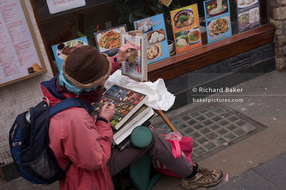 Street artist works outside Chinese restaurant in London's Chinatown.