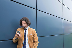 Man business suit cell phone reading SMS