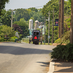 Intercourse, PA - June 17, 2012: A horse-drawn Amish buggy  travels on a road in Lancaster County.