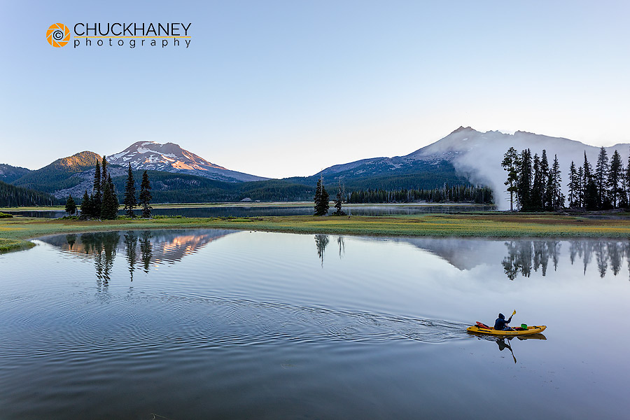 Kayaker paddles on Sparks Lake at dawn n the Deschutes National Forest near Bend, Oregon, USA