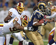 Washington Redskins defensive linemen Phillip Daniels (L) makes a diving tackle from behind on St. Louis Rams running back Steven Jackson (R) for a short loss in the first quarter, during the Redskins 24-9 win at the Edward Jones Dome in St. Louis, Missouri, December 4, 2005.