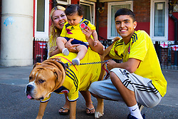 Outnumbered but hoping for victory, A Colombian family and their dog Troy are pictured on the Kirby Estate in Southwark where local residents have put on a huge display of support for England in the World Cup. PICTURED: Mother Sandra Ramos, 48, her Grand-daughter Adeline, seven months, and her Son Jean-Paul Jhonnes, 19 with Troy their American Boxer Dog . London, July 02 2018.