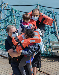 © Licensed to London News Pictures. 03/08/2021. Dover, UK. Young migrants are helped ashore by a Border Force officer at Dover Harbour in Kent after crossing the English Channel. Hundreds of migrants have made the crossing in recent weeks. Photo credit: Stuart Brock/LNP